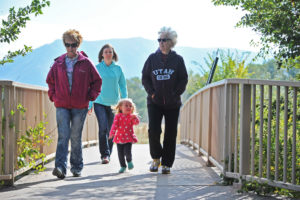 A family walks along the Portneuf Greenway trail at the Edson Fichter Nature Area.